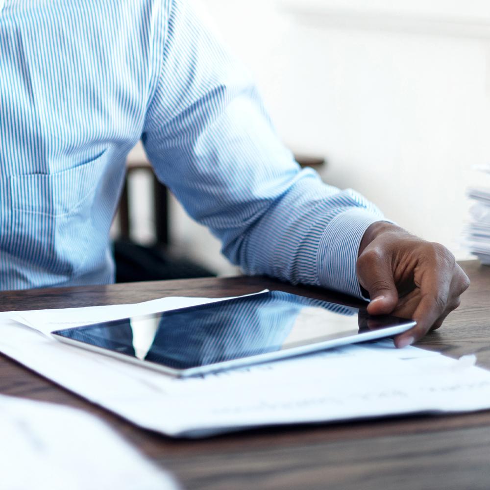 Man holding tablet at desk